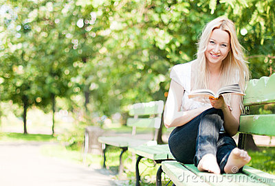 young-woman-reading-book-park-14822722
